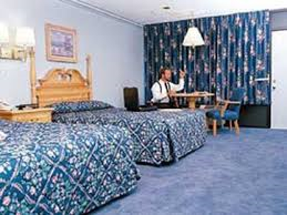 inside one of the rooms, showing 2 beds and a man at a table