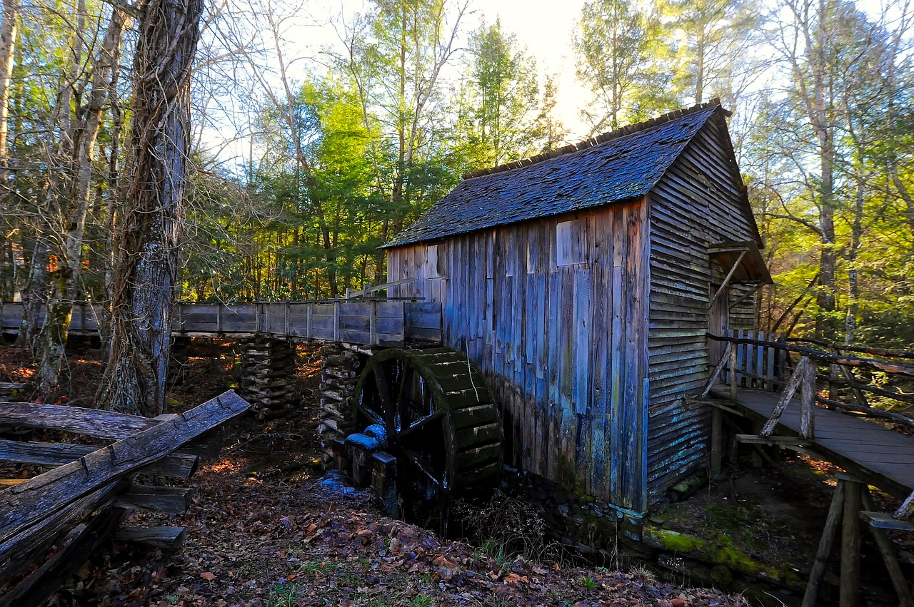 photo shows an old water mill with a small wooden cabin attached