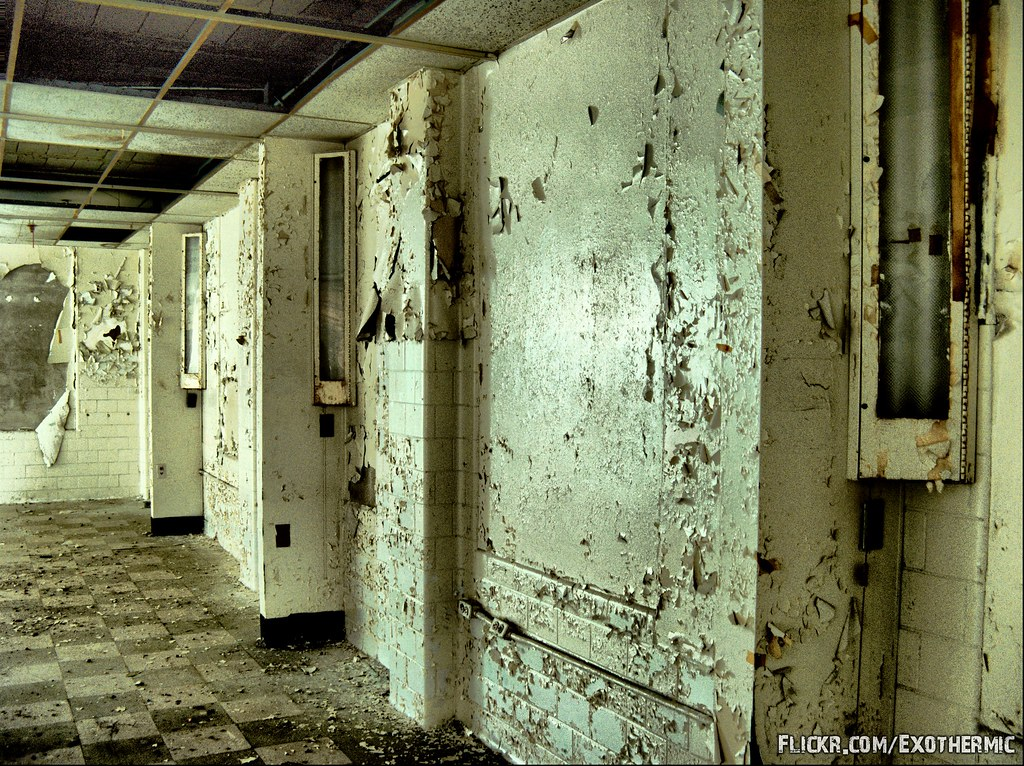 photo shows a hallway with peeling paint and rust dripping down the walls.