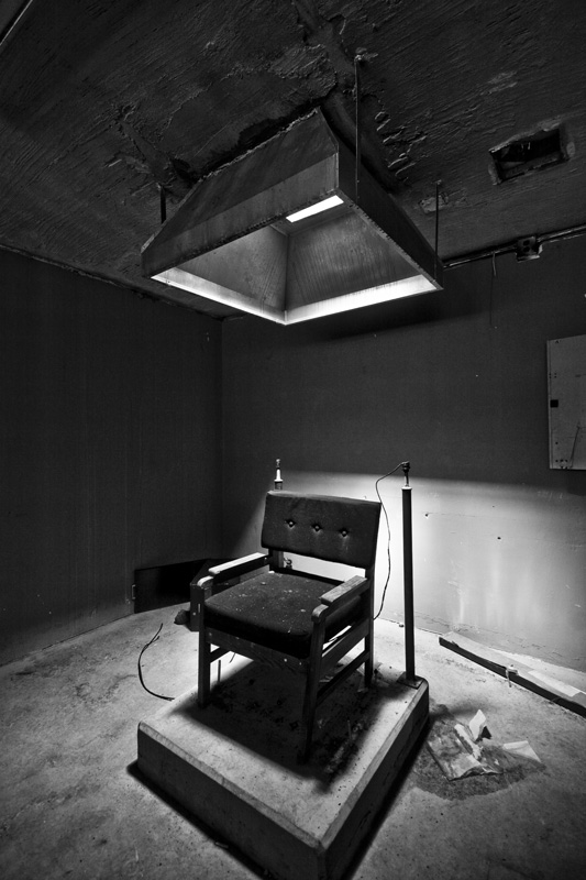 photo shows an old electric chair sitting in a dark room in black and white.