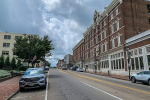 Photo shows a street view of the General Morgan Inn, a grand brick structure with three floors and a street level of shops. Cars are parked outside on the street, and a cloudy sky is behind.