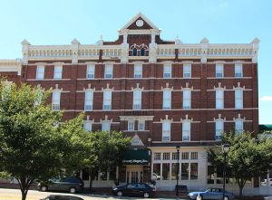The General Morgan Inn from the front, grandiose and made of red brick. White accents surround the windows and small trees dot the façade of the building.